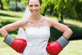 Bride wearing boxing gloves with hands on waist portrait of young in garden Royalty Free Stock Image