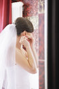 Bride wears earring while standing in bathroom Stock Photos