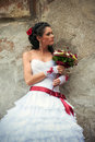 Bride with wedding bouquet leaning against the wall Royalty Free Stock Image