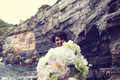 Bride with wedding bouquet on the shore Royalty Free Stock Photo