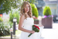 The bride with a wedding bunch of flowers red bouquet in park Stock Photos