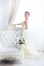 Bride in wedding dress and flowers the sits on a antique chair with a bouquet a indoor Royalty Free Stock Photos