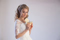 Bride in wedding dress holding a chocolate
