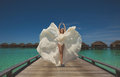 Bride in wedding dress in the maldives jumping and having fun on tropical island of Royalty Free Stock Images