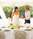 Bride with wedding planner in marquee smiling Royalty Free Stock Photo