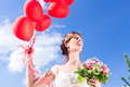 Bride at wedding with read helium balloons Stock Photo
