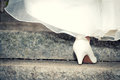 Bride in wedding shoes and dress on stairs close up Royalty Free Stock Photography