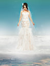 Bride in wedding white dress standing on a cloud and looking to the ground Stock Image
