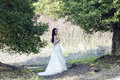 A bride with white wedding dress stand in the middle of trees Royalty Free Stock Photo