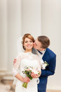 The bridegroom kisses the bride that stands between the columns of the old building Royalty Free Stock Photo