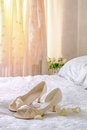 The brides sandals on bed with wedding dress hanging in background Stock Images