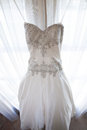 Brides wedding dress hanging from a window Stock Photo