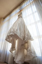 Brides wedding dress hanging from a window Royalty Free Stock Photos