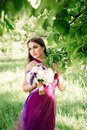 Bridesmaid with luxurious colorful fine art wedding bouquet of peonies and other flowers standing at the ceremony near