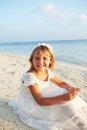 Bridesmaid sitting on beach at wedding ceremony smiling to camera Royalty Free Stock Photography