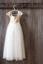 Bridesmaids dress little girls hanging from hook on wooden panelled wall Stock Photo