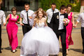 Bridesmaids and groomsmen look at a kissing wedding couple stand Royalty Free Stock Photo