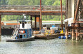 Bridge barge a small tugboat moves a during the construciton of the new sellwood in porland oregon Stock Photos