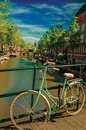 Bridge on canal with bike stuck at balustrade and moored boats under blue sky in Amsterdam.