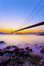 Bridge at coast with sea stones in sunset it is a scene hong kong under tsing ma Stock Photo
