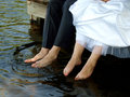 Bridge groom feet hanging off dock water Royalty Free Stock Photos