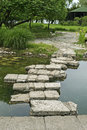 Bridge made of flagstones over puddle Royalty Free Stock Photo