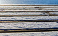 Bridge made of plank with snow and ocean low angle view a partly covered glimps the Stock Images
