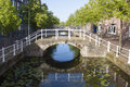 Bridge over canal with reflection and trees Royalty Free Stock Image