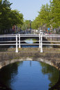 Bridge over canal with reflection and trees Stock Photo