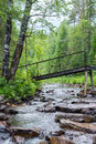 A bridge over a small stream with large rocks in the green forest. Royalty Free Stock Photo