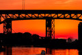 Bridge over sunset a small boat sails under a silhouetted highway into the lake erie at cleveland Royalty Free Stock Photography
