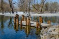 Bridge on the pond wooden pillars with chain in early spring Royalty Free Stock Photo