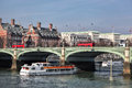 Bridge with red buses against city cruise ship in London, England, UK Royalty Free Stock Photo