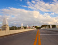 Bridge road with yellow dividing line on a beautiful summer day clouds and blue sky in miami beach florida Royalty Free Stock Photos