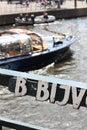 Bridge sign along the Amstel, tour boat passing under bridage Royalty Free Stock Photo