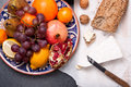 Brie cheese with bread and fruits grain nuts on dark surface Royalty Free Stock Photos