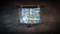 Briefcase filled with dollar packs elegant open on a wooden desktop in the dark top view Stock Photography