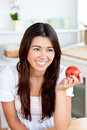 Bright asian woman holding an apple in the kitchen Stock Photo