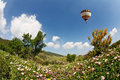 A bright balloon flying over hills huge scenic blooming buttercups Stock Photos