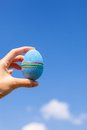 Bright beautiful easter egg in hand on background blue of blue sky Stock Photography
