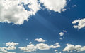 Bright blue cloudy sky with sunbeams from clouds Royalty Free Stock Photo