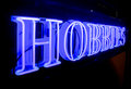 A bright blue hobbies neon sign saying at night Royalty Free Stock Photo