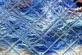 Bright blue wool is reflected in a glass tile
