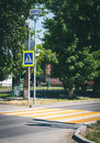 Bright blue and yellow pedestrian crosswalk sign on a town street with traffic warning. Royalty Free Stock Photo
