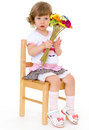 Bright bouquet of spring flowers in the hands a charming little girl who is sitting on a wooden chair and fun ulybaetsya Royalty Free Stock Photography