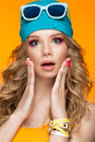 Bright cheerful girl in sports hat, colorful make-up, curls and pink manicure. Beauty face. Royalty Free Stock Photo