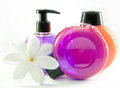 Bright color cosmetic small bottles with the dispenser and white flower Royalty Free Stock Photos