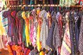 Bright colored children`s dresses or sarafans hang on hangers and are sold in the market of bazaars in India. Showcase with Royalty Free Stock Photo