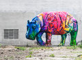 Bright colored hippopotamus graffiti on a gray brick wall.