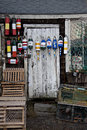 Bright colorful bouys hanging on a rustic shed surrounded by wood lobster traps and cages Stock Image